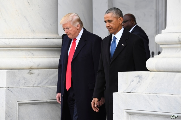FILE - President Donald Trump walks with former President Barack Obama on Capitol Hill in Washington.