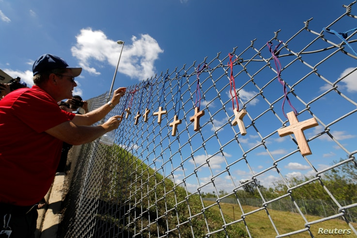 Bob Ossler, chaplain with the Cape Coral volunteer fire department, places 17 crosses for the victims of Wednesday's shooting at Marjory Stoneman Douglas High School on a fence a short distance from the school in Parkland, Florida,  Feb. 15, 2018.