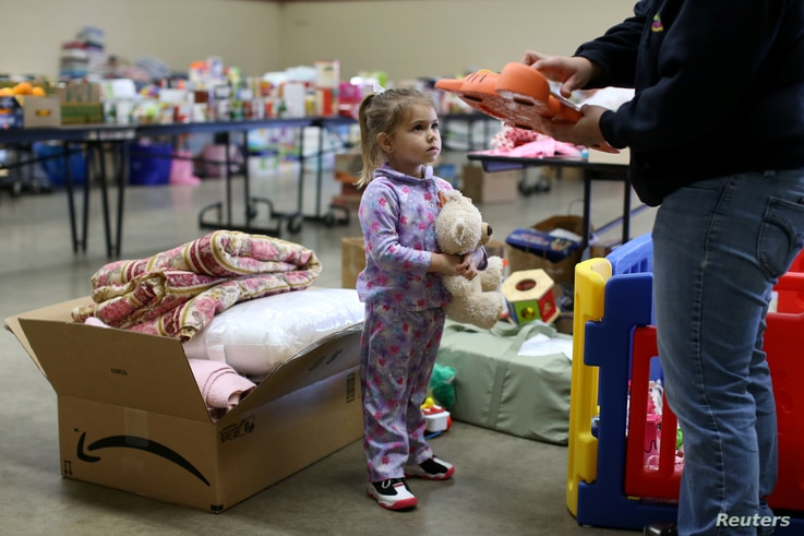 Emma Neurohr, 4, of Oroville, watches her mother at the Salvation Army relief center at the Placer County Fairgrounds in Roseville, California, after an evacuation was ordered for communities downstream from the dam in Oroville, Calif., Feb. 14, 2017...