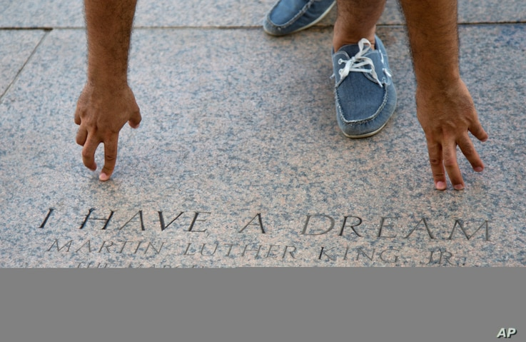 A tourist points to the exact location where Rev. Martin Luther King Jr., gave his famous 'I Have a Dream' speech, at the Lincoln Memorial in Washington, Aug. 22, 2013.