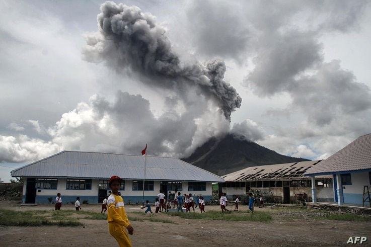 Children play at an elementary school as the Mount Sinabung volcano spews smoke in Karo on November 13, 2017.