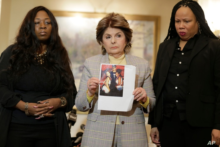 FILE - Latresa Scaff, right, and Rochelle Washington, left, look on as attorney Gloria Allred holds up a picture of them as teenagers on the night they claim they became victims of musician R. Kelly's sexual advances during a news conference in New Y...