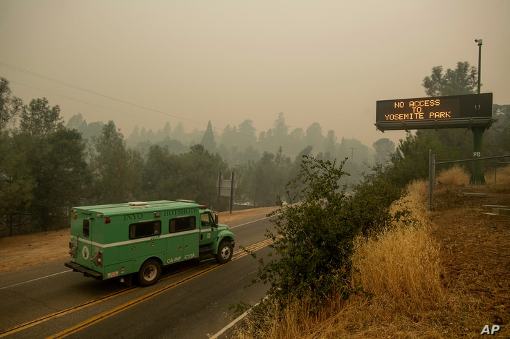 A fire transport drives along Highway 140, one of the entrances to Yosemite National Park, in Mariposa, Calif., July 16, 2018.