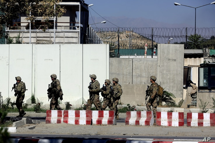 U.S. military forces stand guard at the site of a suicide attack near a U.S. military camp in Kabul, Afghanistan, Tuesday, Sept. 16, 2014. A Taliban suicide car bomber attacked a foreign motorcade just a couple hundred yards (meters) from the U.S. Em