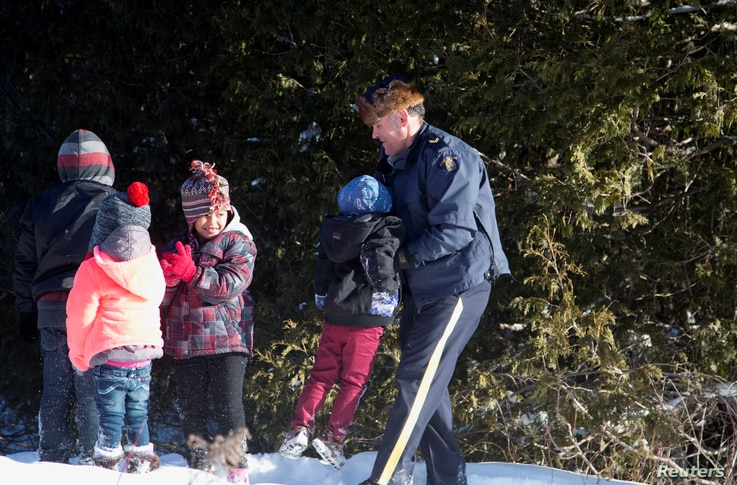 A Royal Canadian Mounted Police officer assists a child from a family that claimed to be from Sudan as they walk across the U.S.-Canada border into Hemmingford, Canada, from Champlain, New York, Feb. 17, 2017.