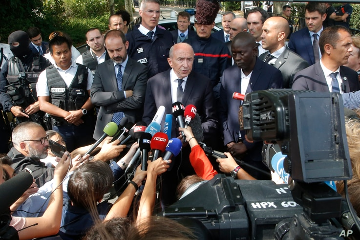 French Interior Minister Gerard Collomb, center, answers reporters after a knife attack Aug. 23, 2018 in Trappes, west of Paris.