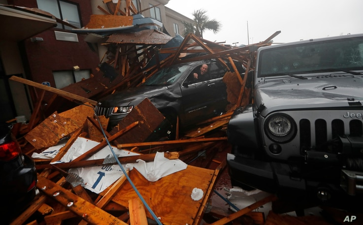 A storm chaser climbs into his vehicle during the eye of Hurricane Michael to retrieve equipment after a hotel canopy collapsed in Panama City Beach, Florida, Oct. 10, 2018.