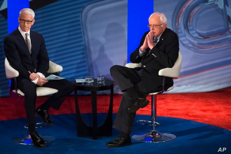 Democratic presidential candidate Senator Bernie Sanders listens to a question from the audience alongside host Anderson Cooper during a Democratic primary town hall sponsored by CNN, in Derry, N.H., Feb. 3, 2016.