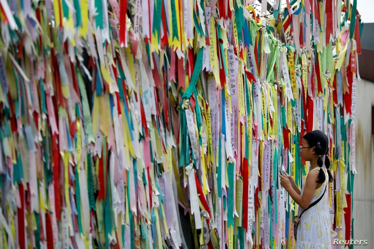 A girl looks at a barbed-wire fence decorated with ribbons bearing messages wishing for the unification between the two Koreas near the demilitarized zone separating the two Koreas in Paju, South Korea.