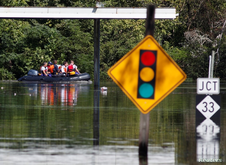 A rescue team navigates its boat through the flooded streets as the Tar River crests in the aftermath of Hurricane Matthew, in Princeville, North Carolina, Oct. 13, 2016.