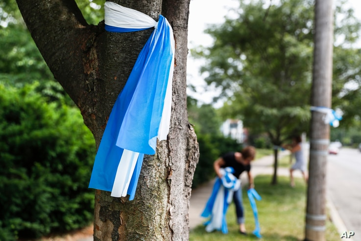 Alison Lebrun, center background, helps tie blue-and-white awareness ribbons near the family home of Otto Warmbier, in the Wyoming suburb of Cincinnati, Ohio, June 13, 2017.