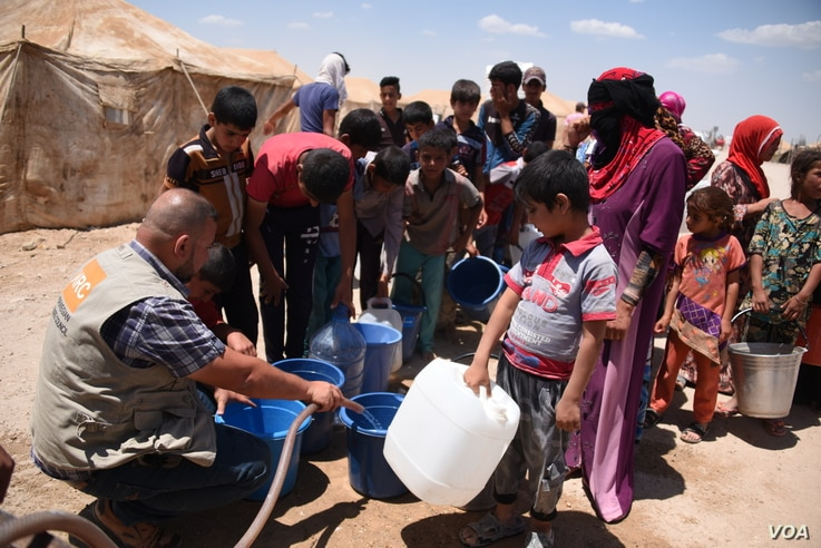 Norwegian Refugee Council staff provide drinking water for Iraqis from Fallujah at Amariyat Al Fallujah displacement camp. Photo: Karl Schembri/NRC