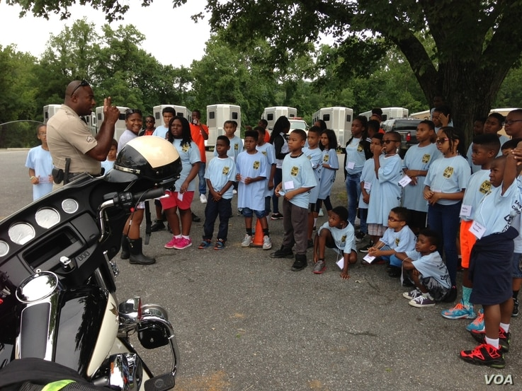 Corporal Randy Green talks with campers about being a motorcycle cop, July 2015. (J. Taboh/VOA)