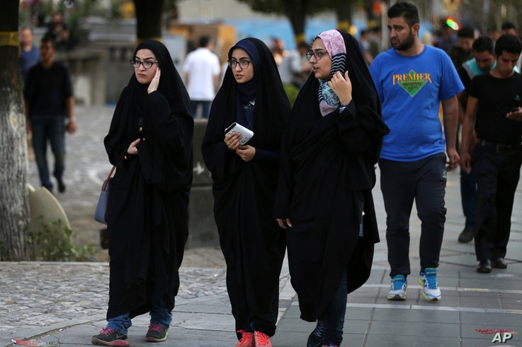 FILE - Iranian women make their way along a sidewalk while wearing chadors, a head-to-toe garment, in downtown Tehran, Iran, Aug. 24, 2017.
