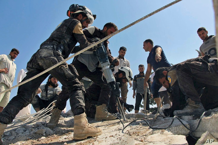 This photo provided by the Syrian Civil Defense White Helmets shows Civil Defense workers using machinery to search through the rubble after airstrikes hit in Khan Sheikhoun, in the northern province of Idlib, Syria, Sept, 24, 2017.