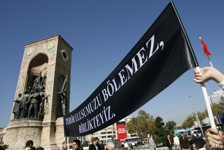 """Lecturers from the Istanbul Technical University display a black banner that reads: """"Terror can't divide our nation, We are together."""" during a protest in Istanbul, Turkey, Oct. 17, 2007."""