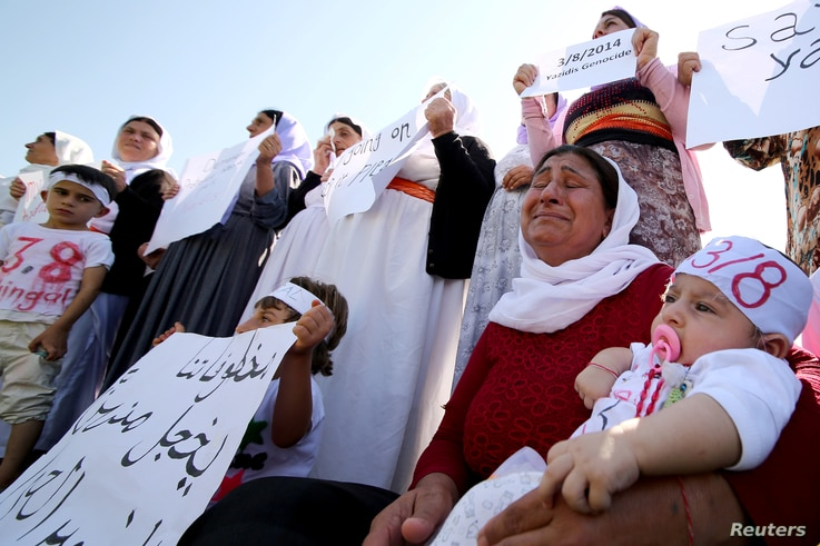 Yazidi women cry as they attend a demonstration at a refugee camp in Kurdish-dominated city of Diyarbakir, Turkey, to mark the second anniversary of what a U.N.-appointed commission of independent war crimes investigators termed a genocide against th...