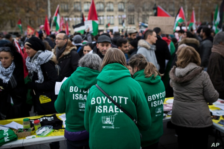 """Demonstrators wear shirts reading """"Boycott Israel"""" during a protest against President Donald Trump's decision to recognize Jerusalem as Israel's capital at Republique Square in Paris, France, Saturday, Dec. 9, 2017."""