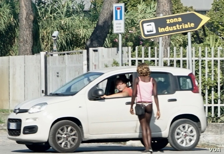 A young Nigerian woman negotiating with a possible client near an industrial zone on Via Bonifica, a busy road linking Ascoli Piceno and the seaside town of San Benedetto de Tronto in Italy's province of Marche.