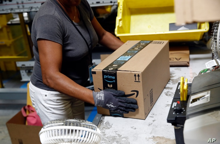 FILE - An Amazon employee applies tape to a package before shipment at an Amazon fulfillment center in Baltimore, Maryland, Aug. 3, 2017.