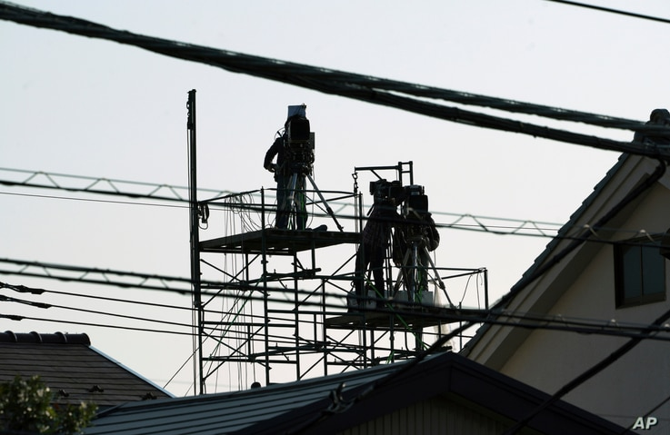 TV cameramen are seen on top of a nearby house in front of Tokyo Detention Center, where former Nissan chairman Carlos Ghosn is detained, March 5, 2019, in Tokyo.