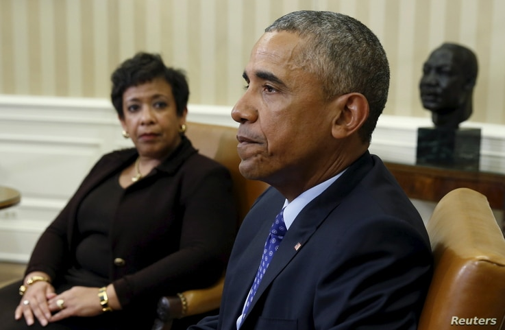 U.S. Attorney General Loretta Lynch (left) looks toward U.S. President Barack Obama during a meeting in the Oval Office of the White House in Washington, Jan. 4, 2016.  Behind Obama is a bust of Martin Luther King Jr.