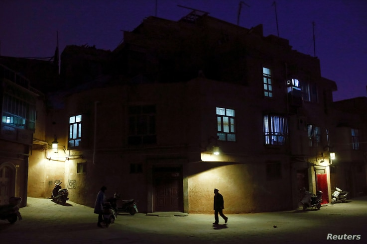 """A man walks along a street at night in the old town of Kashgar, Xinjiang Uighur Autonomous Region, China, March 23, 2017.  Thousands of """"convenience police stations"""" have been built across Xinjiang. They are typically just hundreds of meters apart in..."""