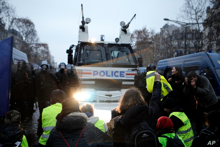 """Demonstrators sit in front of a police water cannon on the Champs-Elysees, Dec. 15, 2018, in Paris. It was the fifth straight weekend of protests by the """"yellow vest"""" movement against France's high cost of living."""