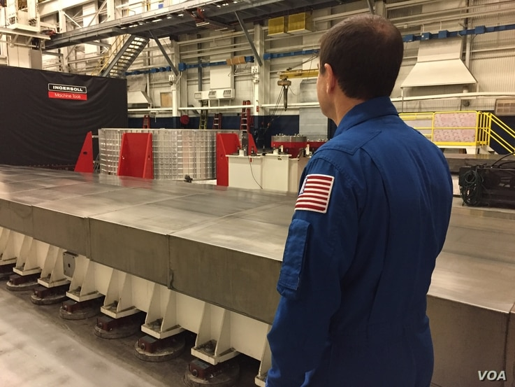 Astronaut Rex Walheim looking at the 'barrel' during a visit to Ingersoll Machine Tools in Rockford, Illinois. (K. Farabaugh/VOA)