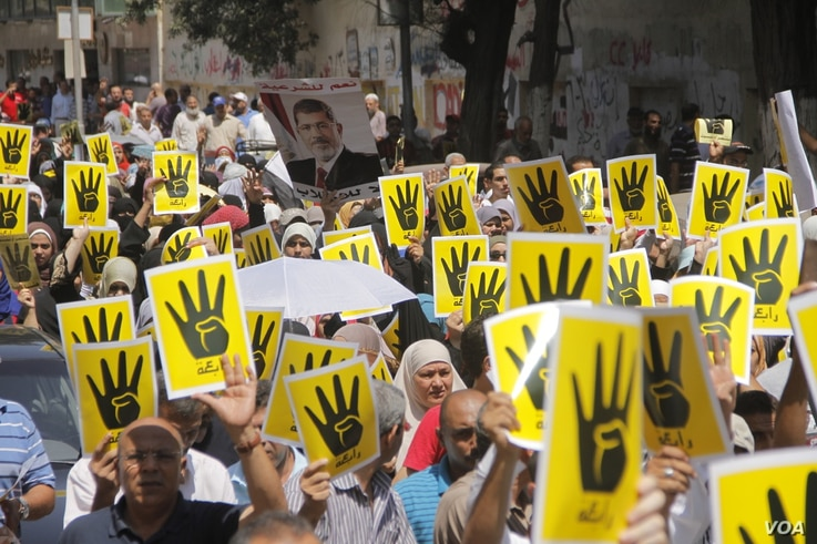 """Demonstrators hold up four fingers, a symbol of their solidarity with the the destroyed sit-in protest known as Rabaa, which means """"fourth"""" in Arabic, Cairo, August 23, 2013. (H. Elrasam for VOA)"""
