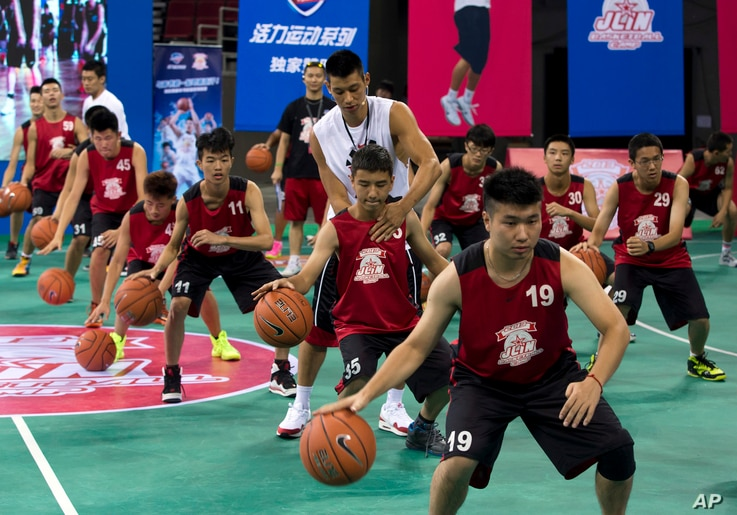 NBA star Jeremy Lin helps a young player during a basketball camp in Beijing, China, Aug. 25, 2013.