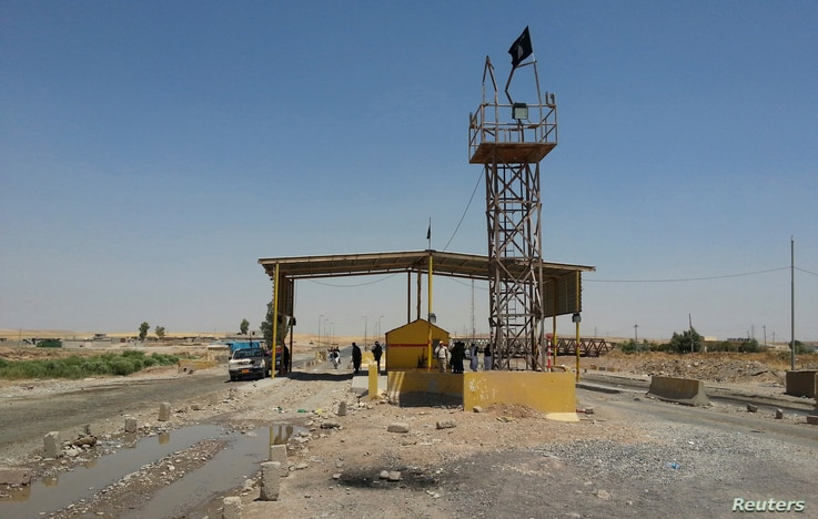 Islamic State militants stand guard after controlling a checkpoint in Khazer at the border area of the Kurdish semi-autonomous region, Aug. 7, 2014.