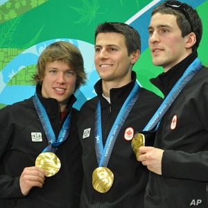 Mathieu Giroux, Lucas Makowsky, and Denny Morrison of Canada show off their gold medals in team pursuit speedskating in Vancouver, Canada, 27 Feb 2010