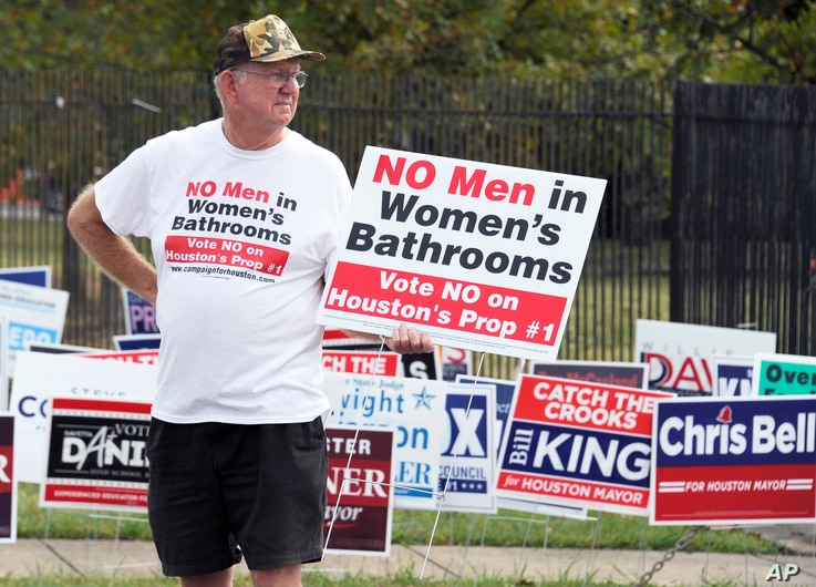"FILE - A man urges people to vote against the Houston Equal Rights Ordinance outside an early voting center in Houston, Oct. 21, 2015. Voters rejected the bill when opponents campaigned on a message of ""No men in women's bathrooms."""