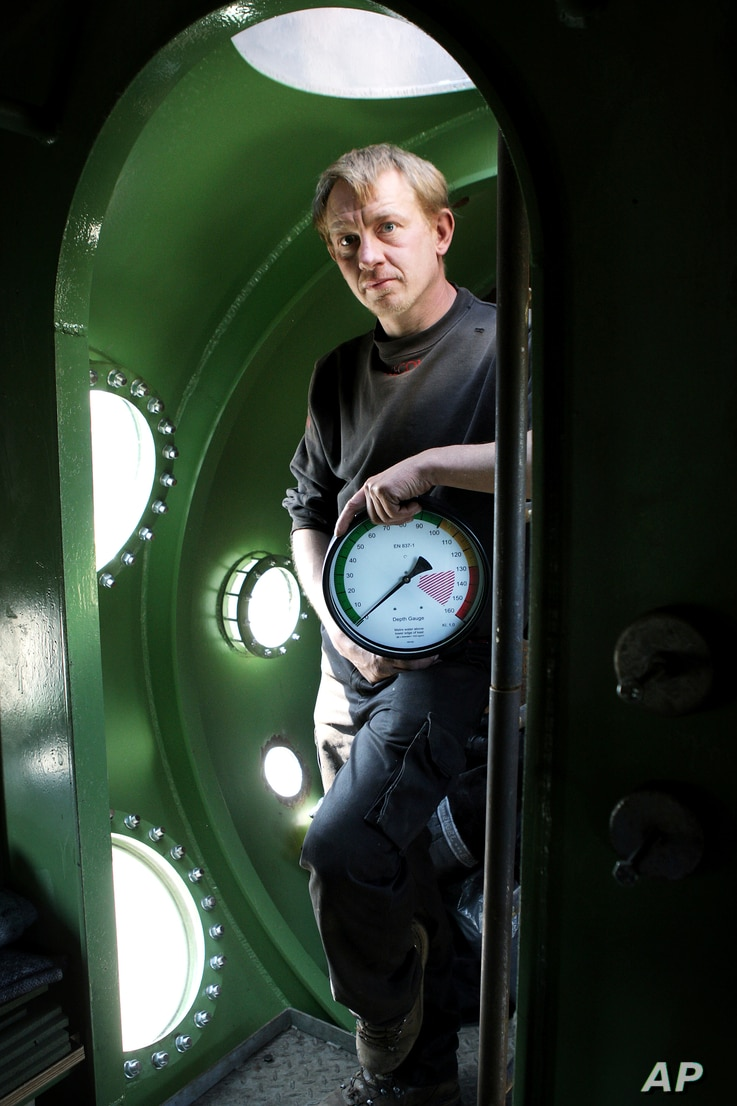FILE - Submarine owner Peter Madsen stands inside the vessel, April 30, 2008. A Danish prosecutor said Madsen has been charged with murdering Swedish journalist Kim Wall during a trip on his private submarine, saying he either cut her throat or stran...