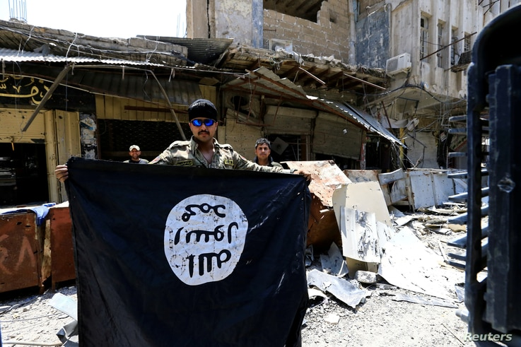 FILE - A member of the Emergency Response Division holds an Islamic State militants flag in the Old City of Mosul, Iraq, July 10, 2017.