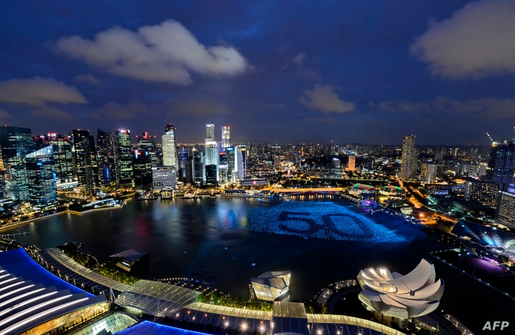Singapore's skyline gliters with lights as spheres in the waters of Marina Bay form the number '50' to mark Singapore's 50th anniversary in 2015, ahead of the New Year's countdown celebrations in Singapore on December 31, 2014. AFP PHOTO / MOHD FYR...
