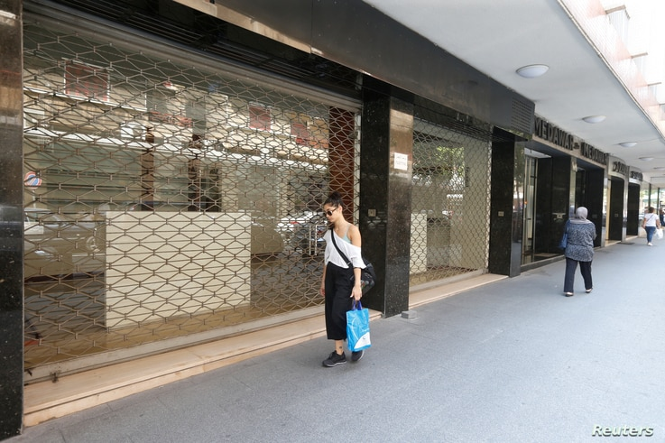 A woman walks past a closed shop in Beirut, Lebanon, Aug. 9, 2018.