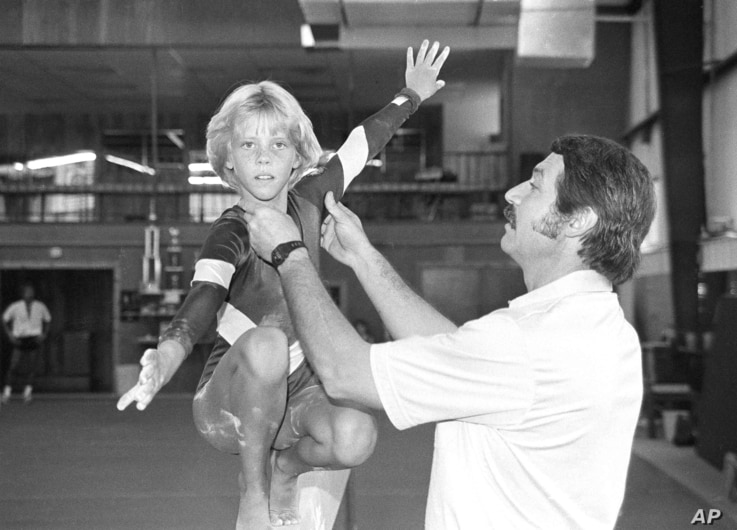 """FILE - In this Aug. 12, 1985, photo, coach Bela Karolyi, right, instructs Sara Tank on the balance beam. When Tank arrived in Houston in 1985, she soon realized that the Bela Karolyi she had seen on television, who was """"animated and acted like he lov..."""