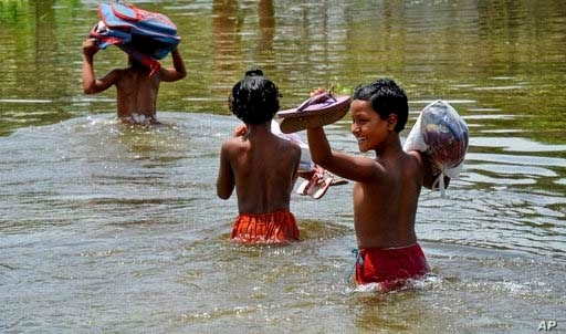Bangladeshi schoolchildren wade past floodwaters in Gaibandha district, about 120 miles (192 kilometers) north of capital Dhaka, Bangladesh, Saturday, Aug. 19. 2017.