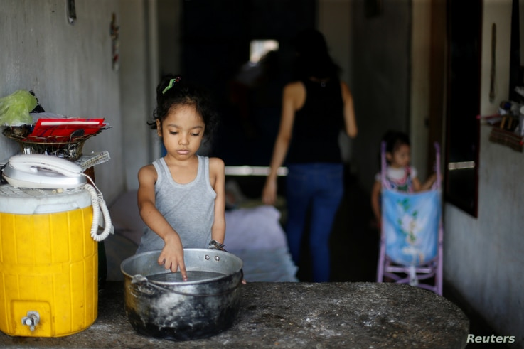 FILE - One of Yennifer Padron and Victor Cordova's daughters touches hot water in a pot in the house where they live at Petare slum in Caracas, Venezuela, Aug. 21, 2017.