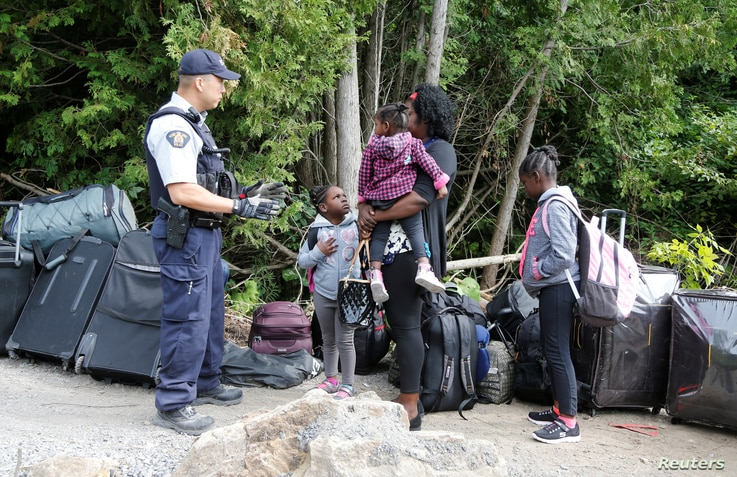 A family who identified themselves as from Haiti are confronted by a Royal Canadian Mounted Police officer as they try to enter into Canada from Roxham Road in Champlain, New York, Aug. 7, 2017.