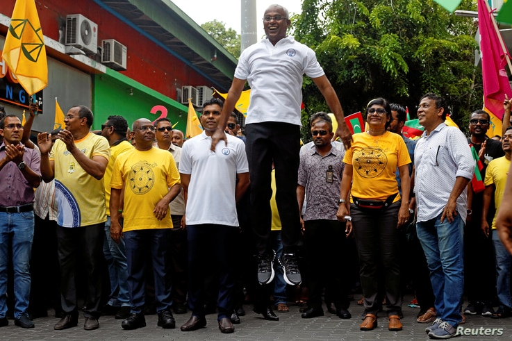 Ibrahim Mohamed Solih, the Maldivian presidential candidate backed by the opposition coalition, jumps next to his supporters during the final campaign rally ahead of the presidential election in Male, Maldives, Sept. 22, 2018.
