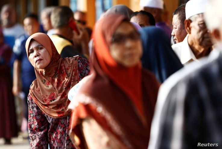People line up to vote during the general election in Alor Setar, Malaysia, May 9, 2018.