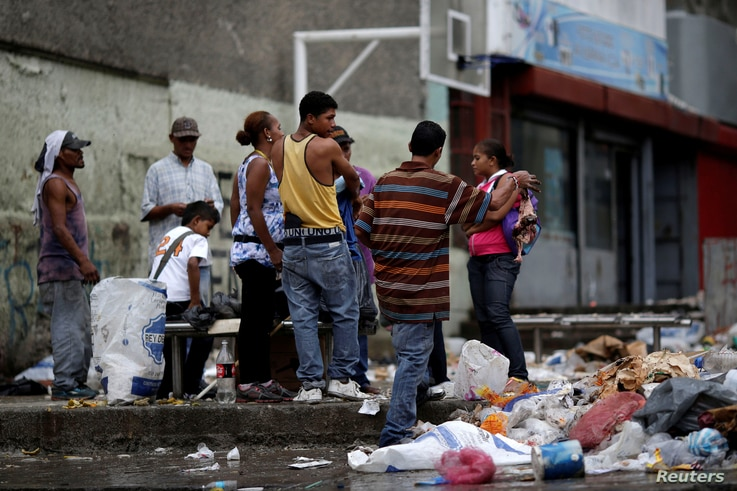 People search through the garbage on a street in Caracas, Venezuela, Nov. 30, 2016. As the economy suffers for a third year, some Venezuelans are forced to forage for food.