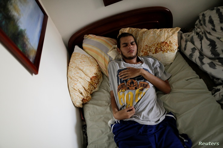 Jesus Ibarra, a 19-year-old engineering student who was injured during a protest against Venezuela's President Nicolas Maduro's government, lies on a bed inside his home in Caracas, Venezuela, Aug. 15, 2017.