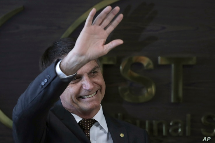 Brazil's President-elect Jair Bolsonaro waves to supporters as he arrives to the Supreme Labor Court in Brasilia, Brazil, Nov. 13, 2018. Bolsonaro, a far-right former army captain, assumes office Jan. 1.