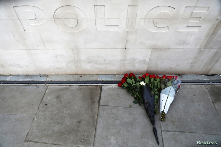 FILE - Flowers are left outside New Scotland Yard after a minute's silence the morning after an attack by a man driving a car and wielding a knife left five people dead and dozens injured, in London, March 23, 2017.