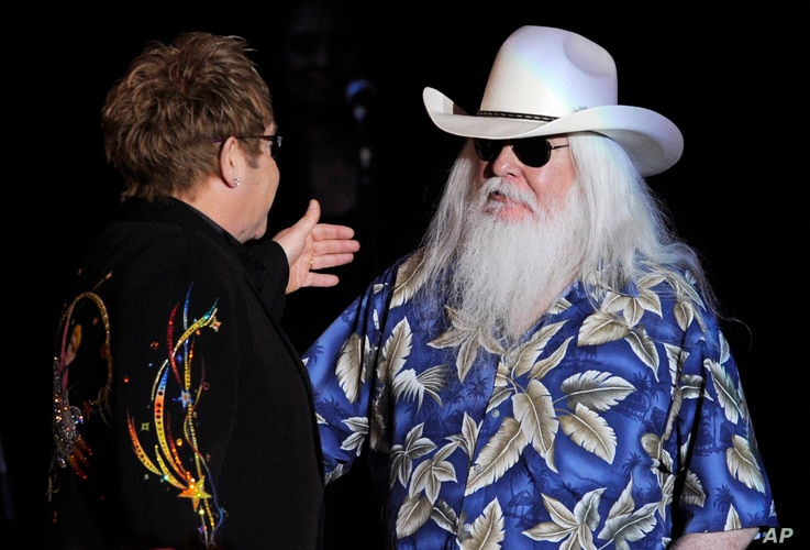 FILE - Elton John, left, greets Leon Russell on the stage during their joint concert at the Hollywood Palladium in Los Angeles, Nov. 3, 2010.