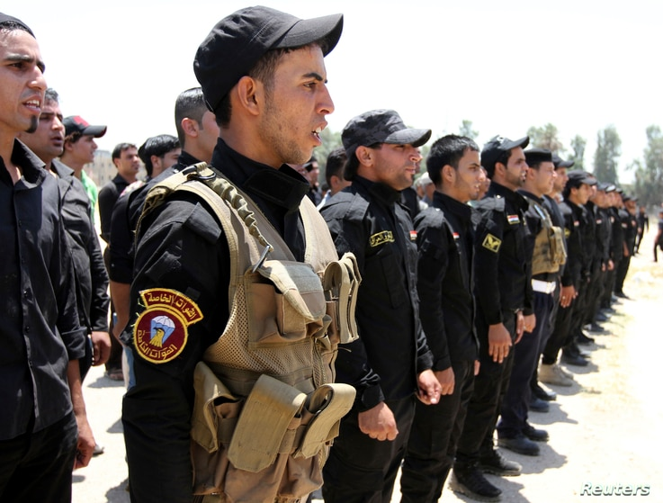 Shi'ite volunteers from Hezbollah Iraq who joined the Iraqi army to fight militants of the Islamic State, formerly known as the Islamic State in Iraq and the Levant, gather together in Baghdad, July 6, 2014.